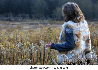 Person standing in a grass field in cold November