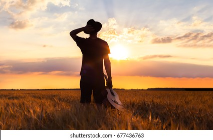 Person standing with his guitar in the warm summer fields looking at sunset for musical inspiration