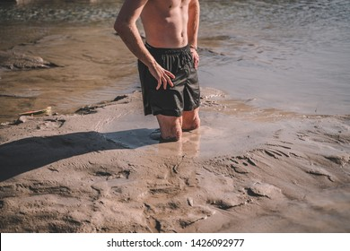 Person standing in natural quicksand river, clay sediments