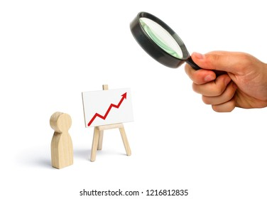 A person is standing near a chart with a red up arrow. Financial success and achievement. Business report and idea. Summarizing. Analysis and market research. Education in economics. Statistical data