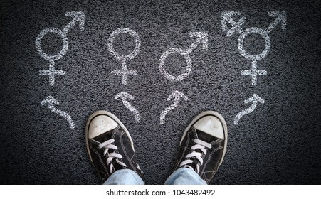 A person standing on asphalt road with gender symbols of male, female, bigender and transgender.  Concept of choice or gender confusion or dysphoria.
