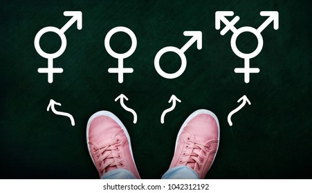 A person standing on chalkboard with gender symbols of male, female, bigender and transgender.  Concept of choice or gender confusion or dysphoria.