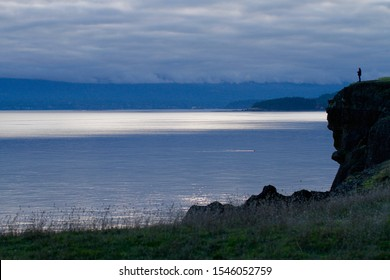 Person standing on a cliff in Halliwell Park on Horby Island overlooking the Salish Sea in British Columbia, Canada.