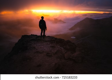 Person standing on the edge of a cliff during sunset while behind a silhouette to the beautiful colors of the clouds around them and the dark rocks leading up towards them in beautiful detail.