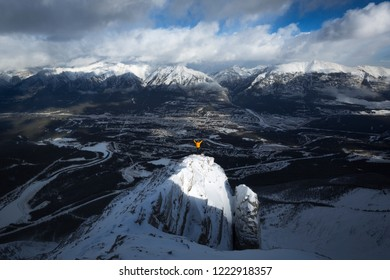 A person standing on Miners Peak above Canmore and The Bow Valley, Alberta, Canada