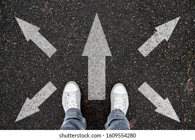 person standing on road with arrow markings pointing in different directions, decision making concept