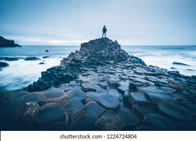 A person standing on the rocks by the sea at the Giant's Causeway, Northern Ireland.