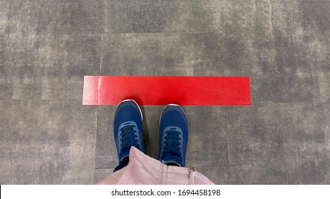 Person standing on tiled floor with a red line. Concept of keep distance, social distancing, quarantine or isolation