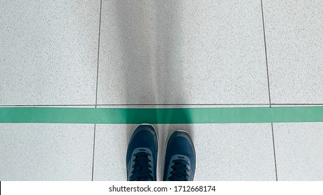 Person standing on tiled floor with a green line. Concept of keep distance, social distancing, quarantine or isolation