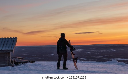 Person standing on top of the mountain at Idre Fjall, Sweden watching a dramatic sunset with his snowboard. View of the valley below with a frozen forest and mountains.
