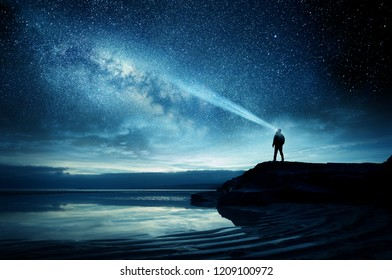 A person standing and watching the Milky Way galaxy rise into the night sky.
