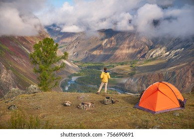 Person stands near the camping and look at the view valley in which there is a river or a creek and a forest. the sky is cloudy, but the weather is sunny.
