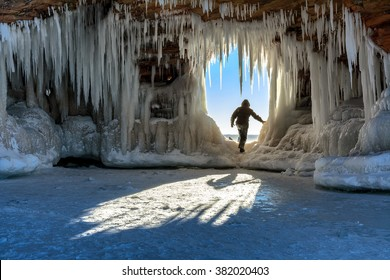 A person steps through an icicle-laden hole in the sandstone formations on Wisconsin's Apostle Islands National Lakeshore near Meyer's beach; Lake Superior.