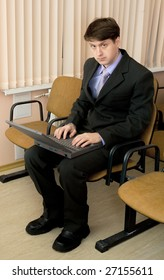 The person in a suit with the laptop in a lap