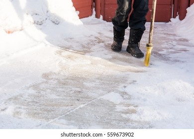 The person sweeps snow with the broom. To sweep away snow