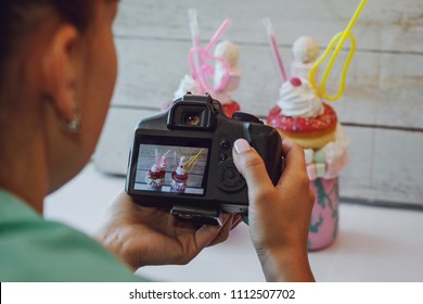 Person take photo with using DSLR camera of glass jars of pink milkshake decorated with donut, cream, candy and marshmallow.