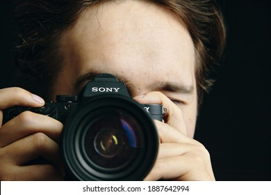 Person takes pictures on Sony camera and tries to focus the lens. Photo editor, cameraman, journalist. Black background. Bishkek, Kyrgyzstan - December 15, 2019.