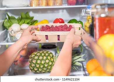 Person taking basket with fresh raspberries from open fridge