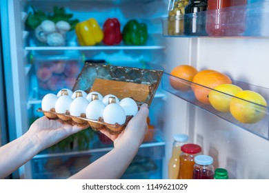 Person taking box with fresh eggs from refrigerator