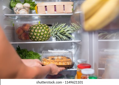 Person taking fresh cake from open refrigerator
