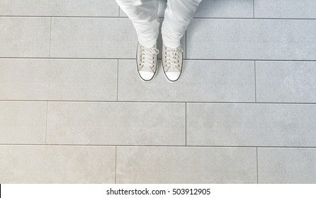 Person taking photo of his feet stand on concrete floor, isolated, top view, clipping path. Ground design mock up. Man wear gumshoes and watching down. Deck flooring mockup template.