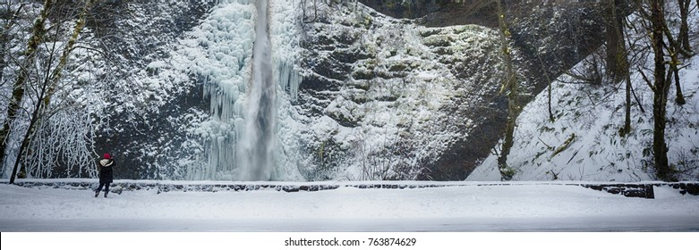 Person taking photo of horsetail Falls in winter, in the Columbia River Gorge, Oregon