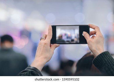 Person taking photo with smartphone, closeup view, copy space.