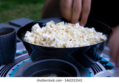 Person taking popcorn from a bowl near teacups outdoors