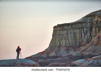 A person taking shoots in colorful Mongolian canyons Tsagaan Suvarga. Bright landscape of a textural striped canyons