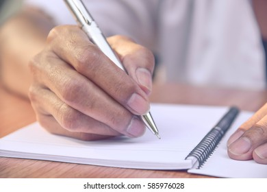 A person is taking some notes into notebooks.