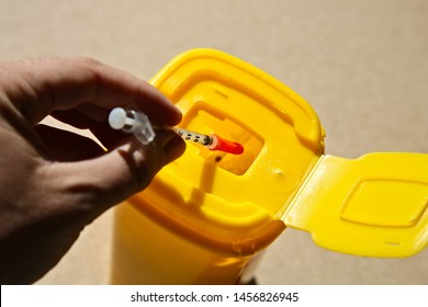 A person throwing away a syringe into a medical waste container.
