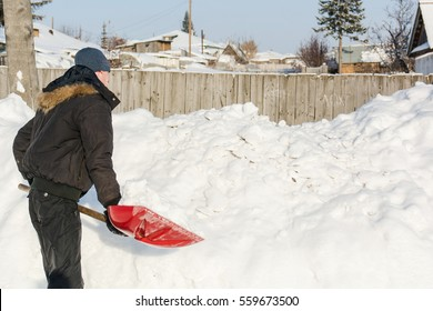The person throws a red shovel snow. Shovels away snow