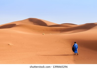 A person in traditional clothing walks through the sand dunes in the Sahara, Morocco, Africa. / A person walks through sand dunes in the Sahara