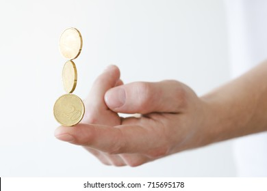Person trying to balance money coins on his finger. Being stable with money.