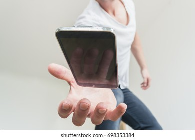 Person trying to catch a phone that drops and is about to fall on the floor. White background. Close up on phone and hand.