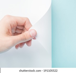 Person turning the white page revealing blue
