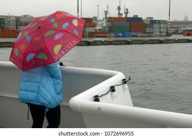 Person with umbrella on a boat in Seattle harbor