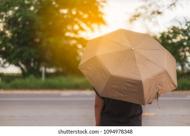 Person and umbrella in summer on street.