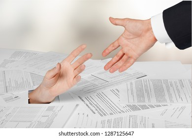 Person under crumpled pile of papers with hand holding a give up sign
