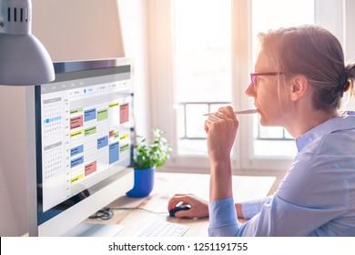 Person, die einen Kalender auf dem Computer verwendet, um die Zeitverwaltung zu verbessern, Termine, Veranstaltungen, Aufgaben und Sitzungen effizient zu planen, die Produktivität zu steigern, Arbeitstage und Arbeitsstunden zu organisieren, Geschäftsfrau, Büro