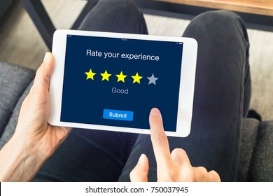 Person using digital tablet computer at home to send customer rating with online website, satisfaction review based on star icons, concept about quality management