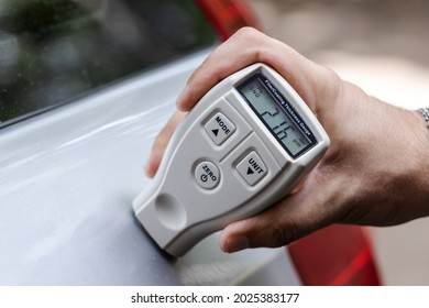 person using film coating thickness gauge device to check car paint. auto coating quality control.