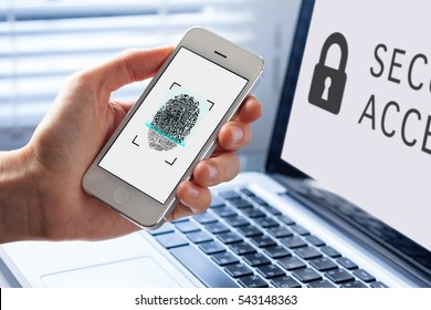 Person using fingerprint scanning on mobile phone for biometrics security, computer in background