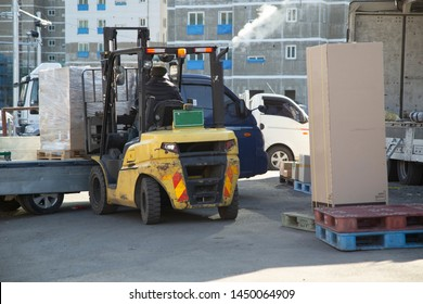 A person using a forklift to drop a cargo from a truck