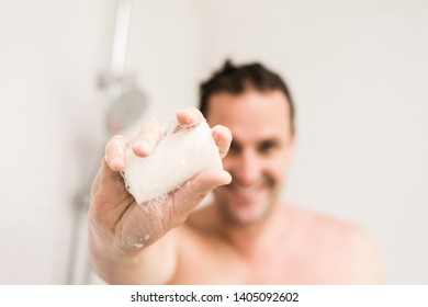 person using hair shampoo soap bar in the shower. A happy man in the shower is holding out the soap bar in front of him. he is blurred in the background.