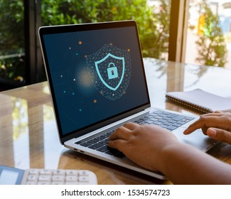 Person using a laptop computer with cyber protection and safe for global network security concept.