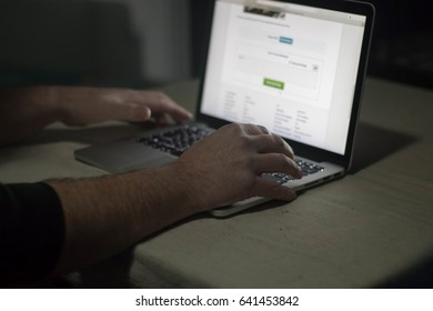 Person using laptop in dark room. Moody, sinister.