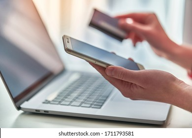 Person using laptop, plastic credit card and mobile phone for online shopping and paying goods. Modern people using e commerce and mobile payment banking