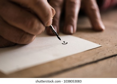 Person using a nib pen and ink to do calligraphy in a close up view of his hands and the first letter drawn on the paper.