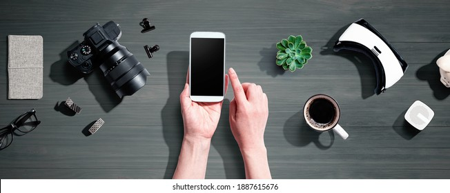 Person using a smartphone with a VR and a SLR camera